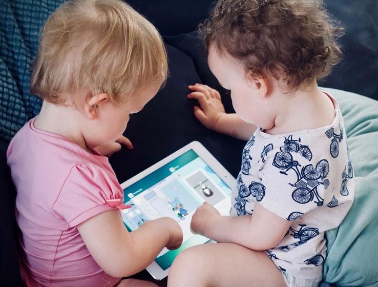 Un restaurante, una mesa redonda, dos o más adultos y los/as niños/as mirando o jugando con la tablet o el móvil.